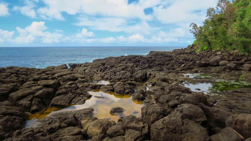 Rocky coast, water pools and blue pacific ocean at Queen`s Bath, Kauai, Hawaii, United States. Rocky coast, water pools, blue sky and blue pacific ocean at Queen royalty free stock images