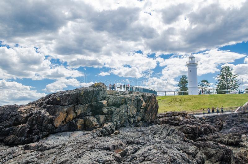 Rocky coastal views with iconic lighthouse at Blowhole Point, south of Kiama Harbour, in cloudy sky day. royalty free stock photos