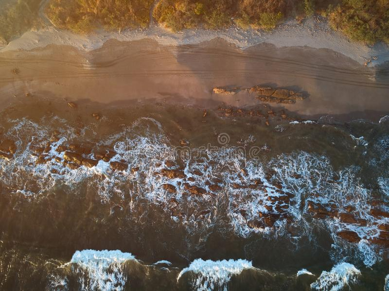 Rocky coastline above top view. On yellow sunset time stock image