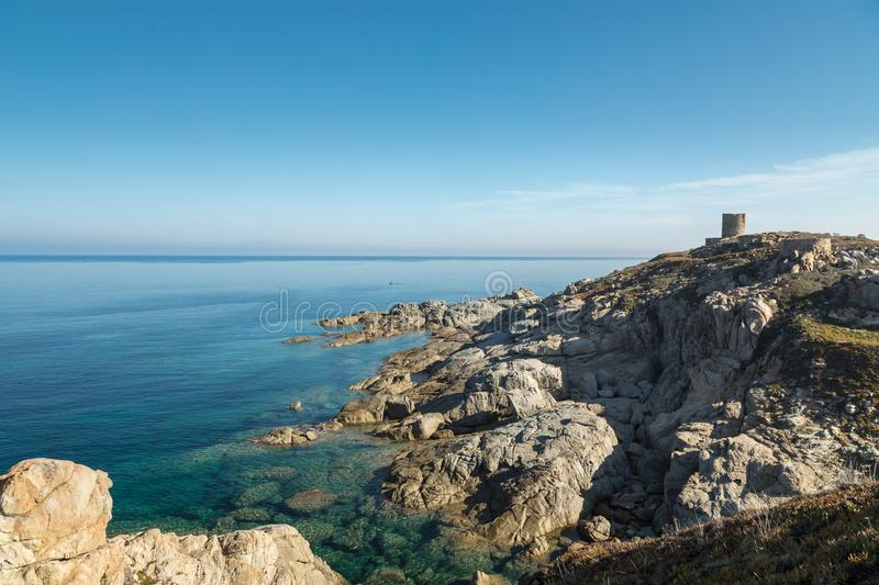 Rocky coastline and Genoese tower at Punta Spano in Corsica. Rocky coastline and transparent turquoise Mediterranean sea below the Genoese tower at Punta Spano stock image