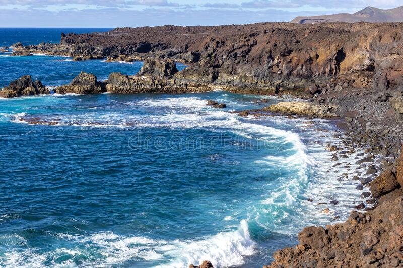 Rocky coastline Los Hervideros in the south west of canary island Lanzarote with rough sea, lava caves and multi colored volcanic stock photos