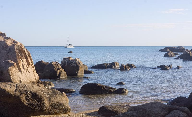 Rocky coastline with ocean and small boat stock image