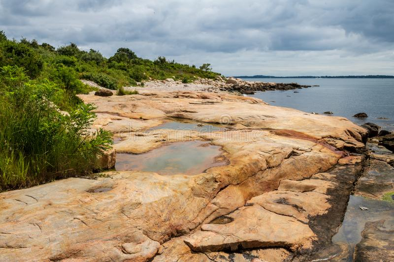 Rocky Connecticut beach on a summer day. Puddles form on large rocks on the Connecticut coastline in Bluff Point State Park stock images