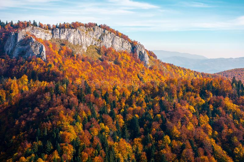 Rocky crag in evening light. Beautiful autumn scenery with fall color foliage in forest royalty free stock images
