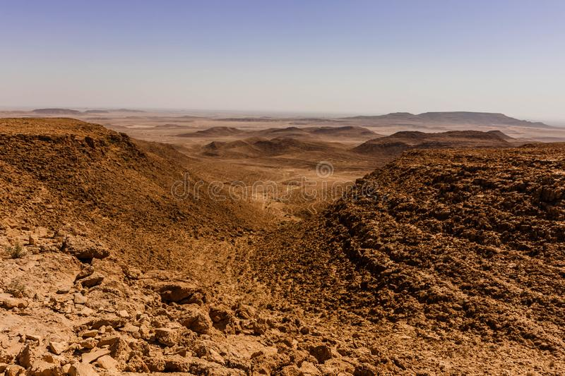 An aerial view of the desert landscape south-east of Riyadh, Saudi Arabia. The rocky desert with a passage between hills as viewed from a plateau in central stock image
