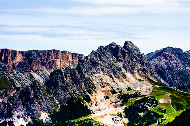 Rocky dolomitic mountains and green valley. In a cloudy summer day royalty free stock images