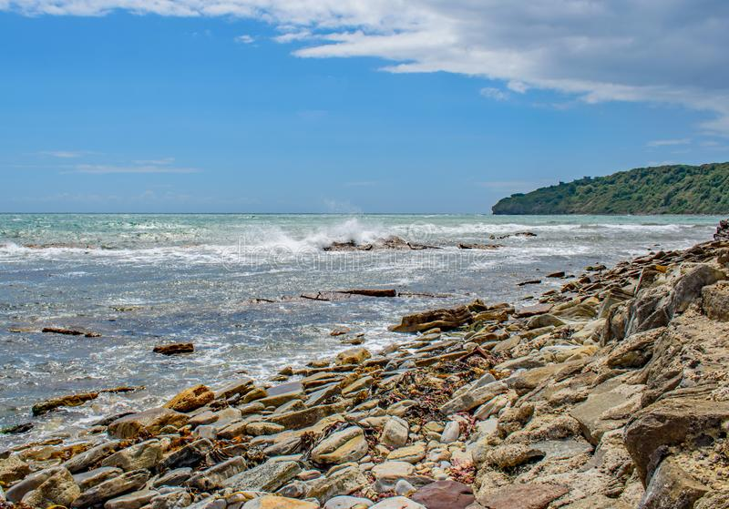 The rocky durasic Swanage coast. Sea spray rises at Swanage Peveril Point against the rocky outcrop royalty free stock photo