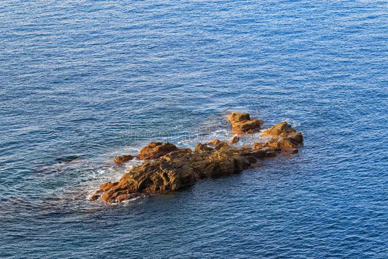Rocky formation in a blue water at sunrise royalty free stock image