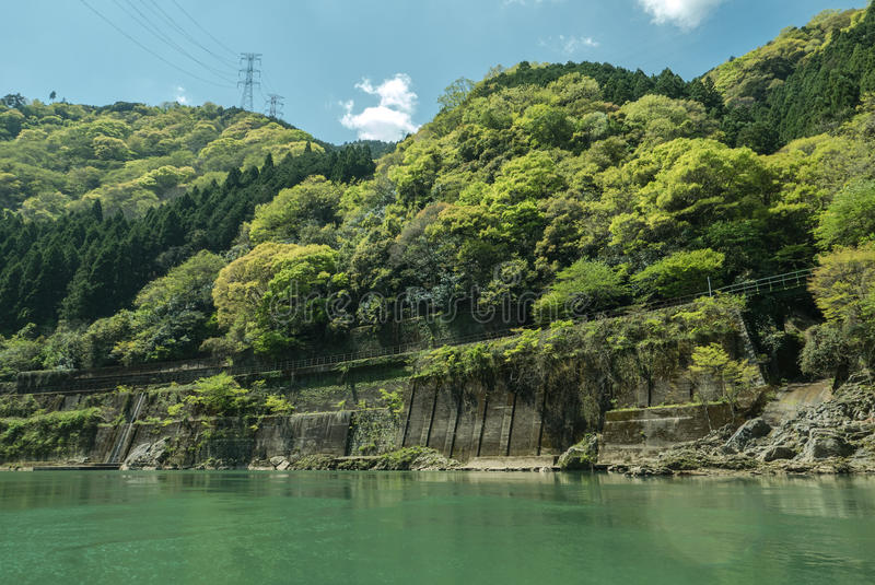 Rocky green hills by Hozugawa River. A view with train tracks and power lines. Arashiyama, Kyoto. Japan royalty free stock images