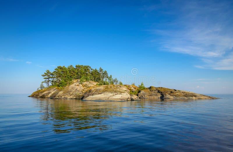 Rocky island. In blue water under blue sky stock image