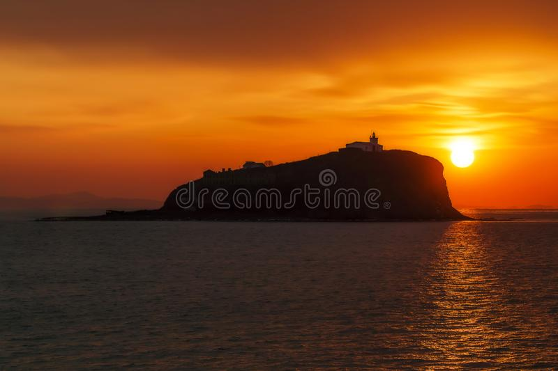 Old lighthouse on the island against the sun royalty free stock photo