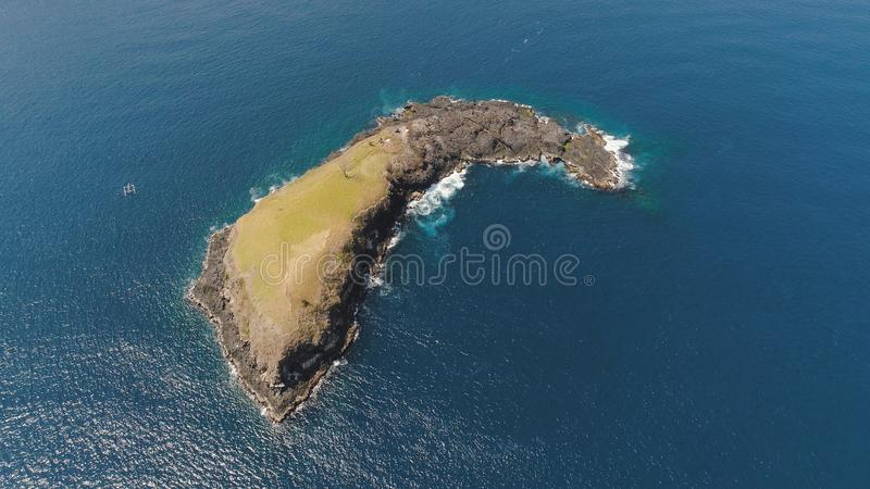 Rocky island in the ocean. Lonely rocky island in the sea. Aerial view Uninhabited tropical island among the ocean. Travel concept stock photography