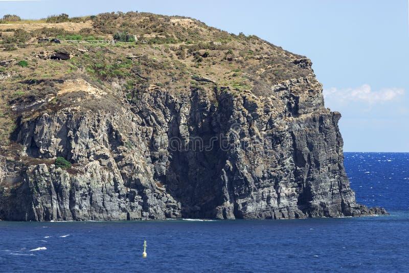 Rocky Island seascape. Blue seascape with a rocky island royalty free stock photos