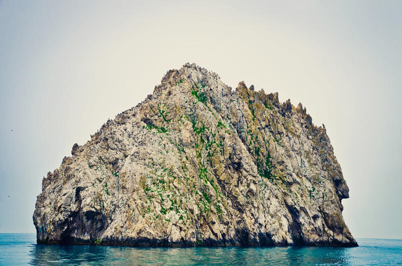 Rocky island. Single rocky island in the sea stock images