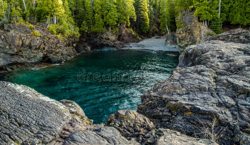 Rocky Lake Superior Cove. The Black Rocks on the shores of Lake Superior are a popular cliff diving location In Marquette, Michigan. The Black Rocks are located royalty free stock photography