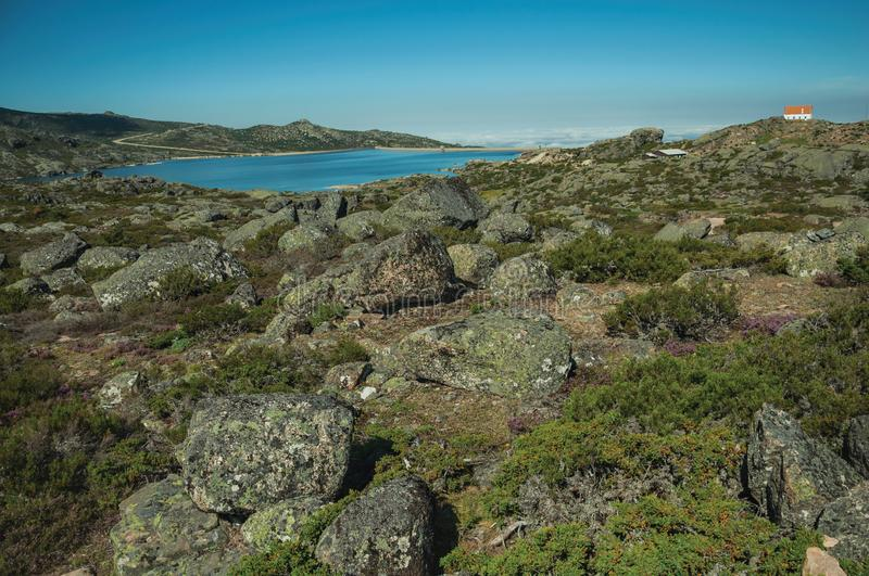 Rocky landscape with lake and house on highlands stock photos