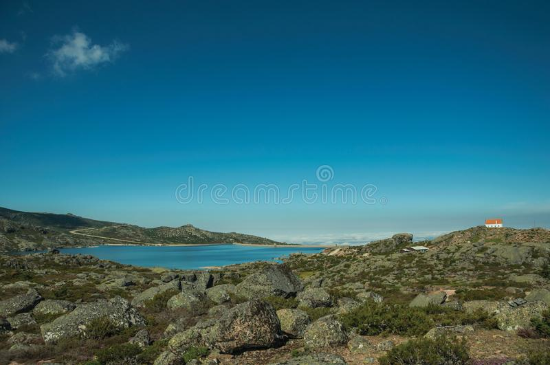 Rocky landscape with lake and house on highlands royalty free stock photos