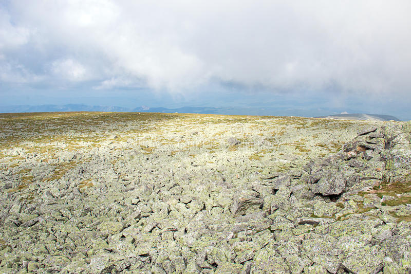 Rocky landscape on the plateau. Field River from stones. Rocky landscape on the plateau in highlands. River from stones, like lunar surface stock photography