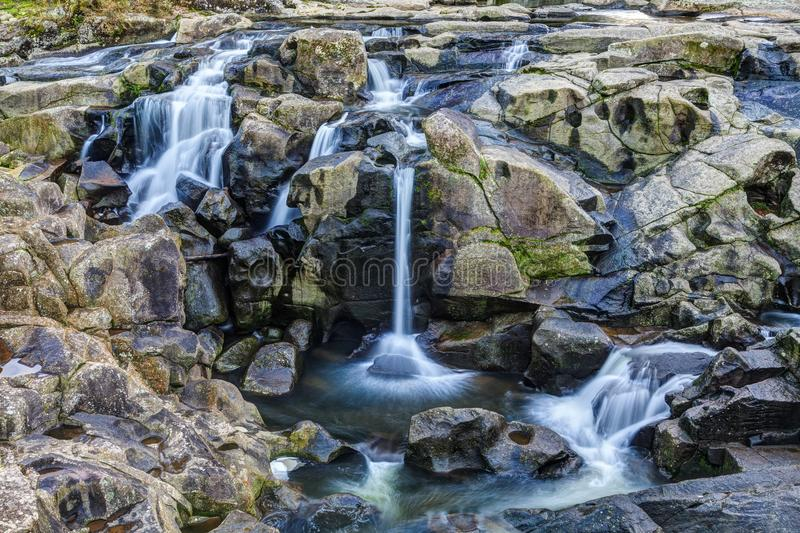 A waterfall with multiple elegant cascades flowing over rocks. A rocky landscape, the stone eroded by water action and speckled with moss. A river breaks up into royalty free stock photo