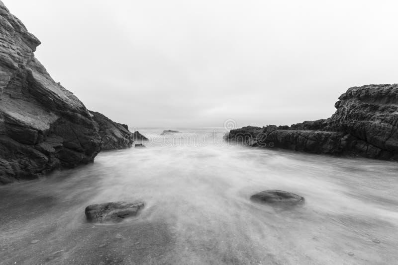 Rocky Malibu Beach med svartvit ub för vatten för rörelsesuddighet royaltyfria bilder