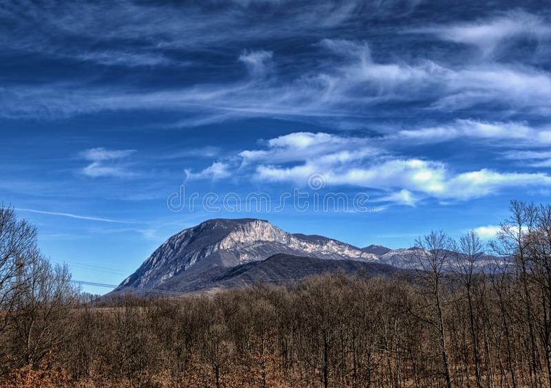 Rocky mountain, bare trees, blue sky with clouds royalty free stock images