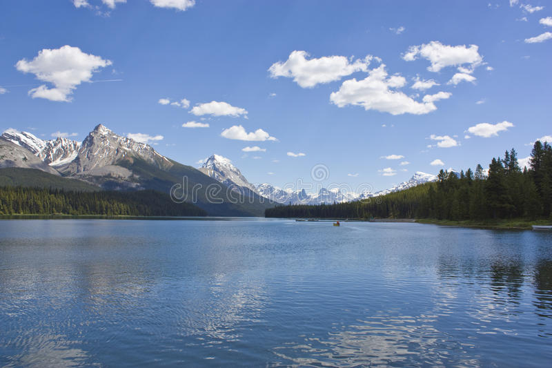 Rocky mountain lake. In Alberta Canada with mountains, white clouds, forest, and canoe in the background royalty free stock image