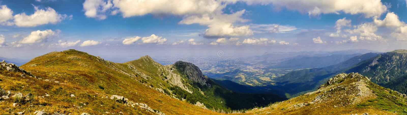 Rocky Mountain Peaks sotto cielo blu con le nuvole bianche panoramiche immagine stock