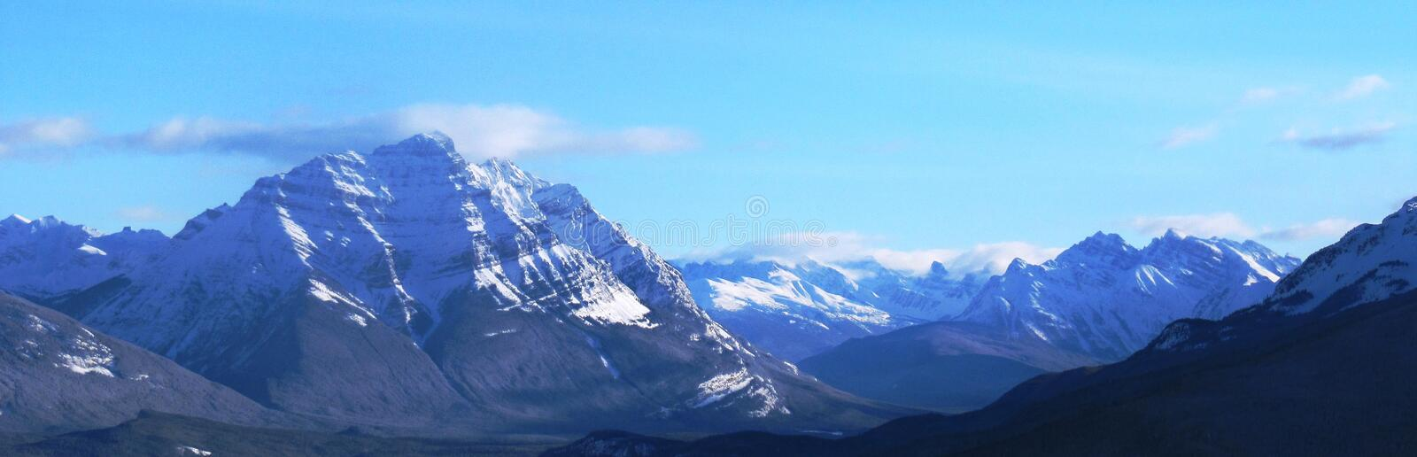 A Rocky mountain scene under a cloudy blue sky stock images