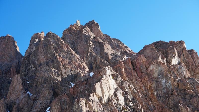 Rocky mountain top. You can see little people. Climbers climb to the top. Large rocks on the sides. Sometimes there is snow. Blue clear sky royalty free stock photos