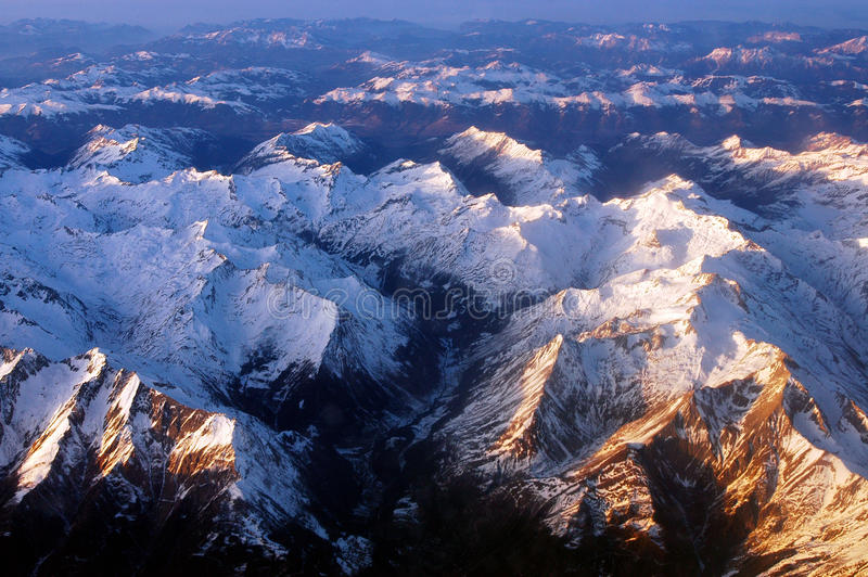 Rocky Mountains. The rocky mountains with its snow peaks from the air under sunset in Switzerland stock photography