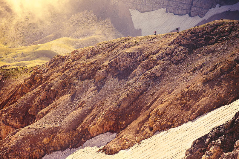 Rocky Mountains with glacier snow and hikers silhouette beyond. Beautiful Landscape Caucasus nature royalty free stock image