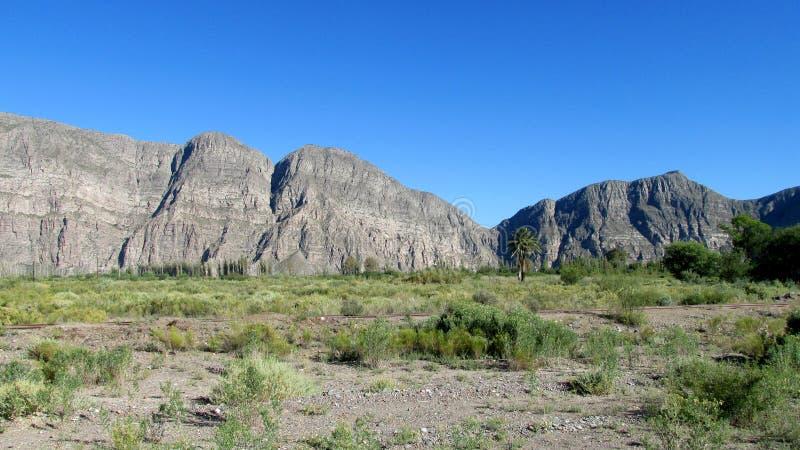 Rocky mountains. Rising above arid flat land royalty free stock photos