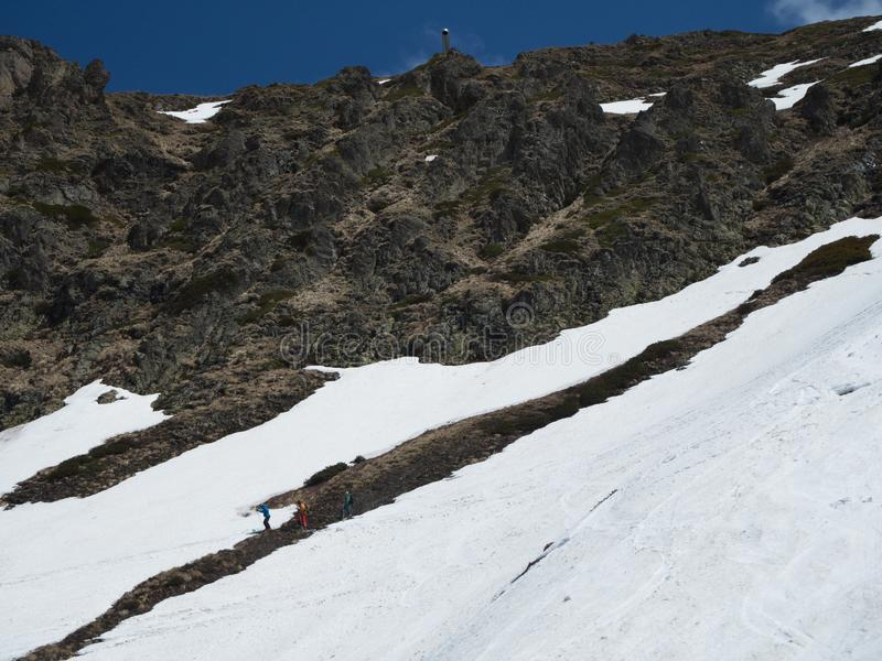 Rocky Mountains ski resort Gorky-gorod. Three skiers under the mountain. Russia Sochi 05.11.2019 stock image