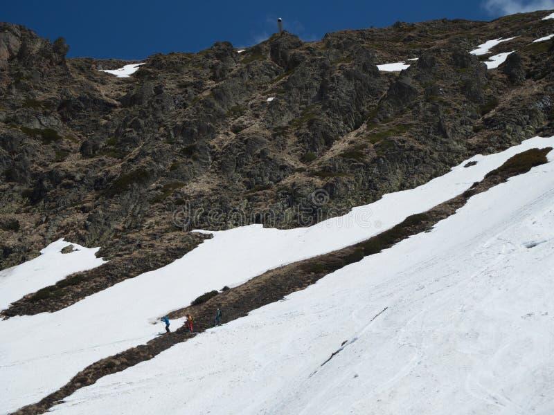 Rocky Mountains-skitoevlucht Gorky -Gorky-gorod Drie skiërs onder de berg Rusland Sotchi 05 11 2019 stock afbeelding