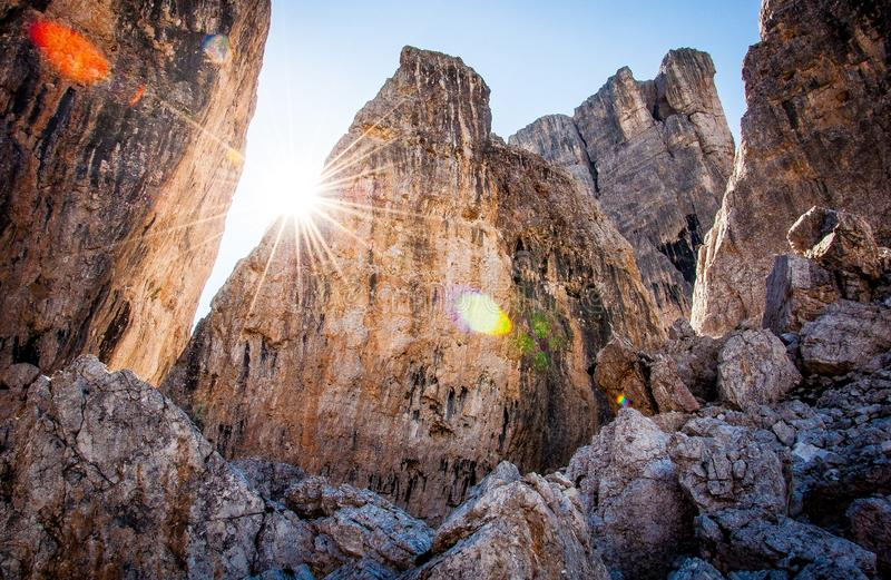 Rocky mountains with sunshine and clear sky in the background in Cortina d'Ampezzo. Low-angle photography of brown rocky mountain under blue sky at daytime in stock image