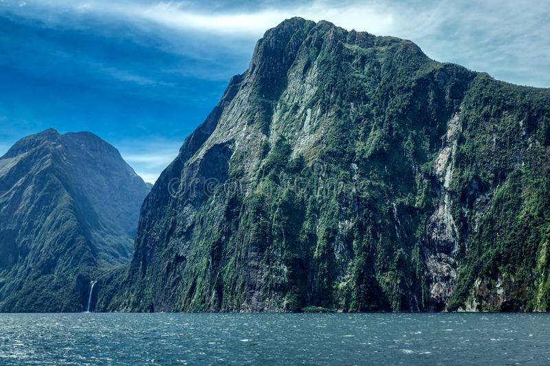 Rocky mountains and waterfall in Milford sound stock photography