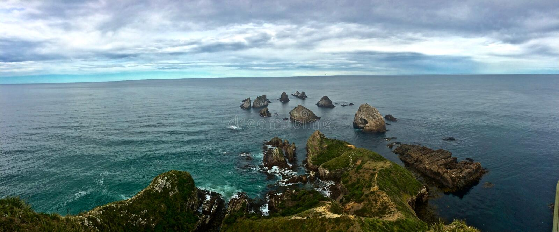 Rocky New Zealand Coastline mit kleinem Rocky Islands Going Out zum Meer lizenzfreies stockfoto