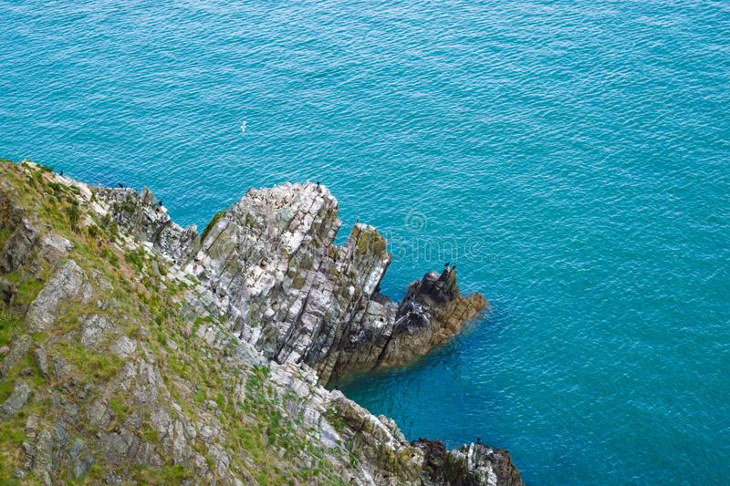 Rocky outcrop at the base of cliffs in Wicklow, Ireland on sunny day in summer. Green hillslide and turquoise-blue Irish Sea. Bright sunny day stock photo