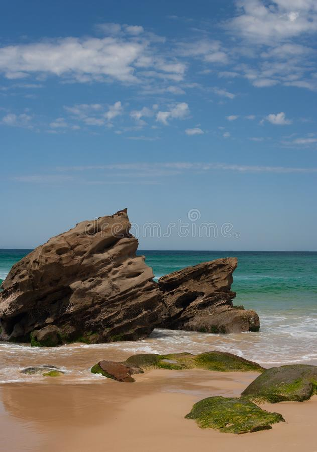 Rocky outcrop at the beach on sunny summers day. With clouds in the sky stock photo
