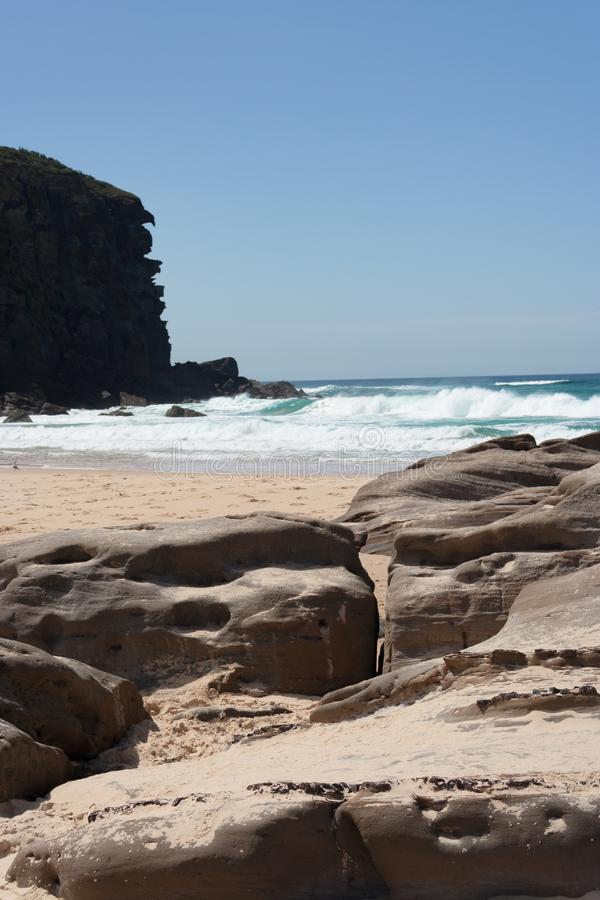 Rocky outcrop and cliff at the beach on sunny summers day. Wuth swimming beach in the middle stock image