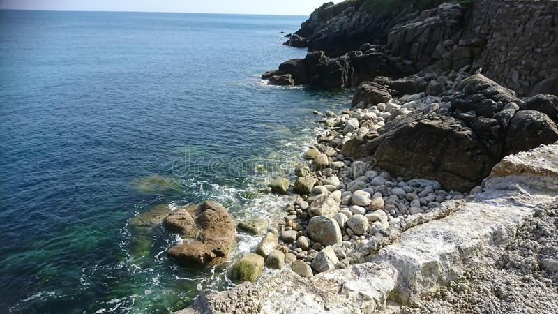 Rocky outcrop ping into the sea royalty free stock photos