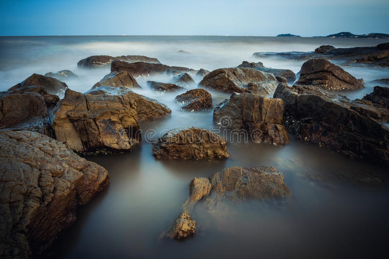 The rocky part in Do Son beach. Seascape from a rocky part of Do Son beach near Ba De pagoda on late afternoon royalty free stock photo
