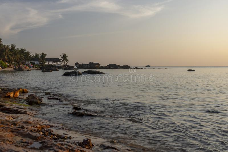 Rocky part of Long Beach on Phu Quoc Island in evening sun. Rocky shore and a calm sea in golden hour with palm trees and a blue sky with some clouds in stock photos