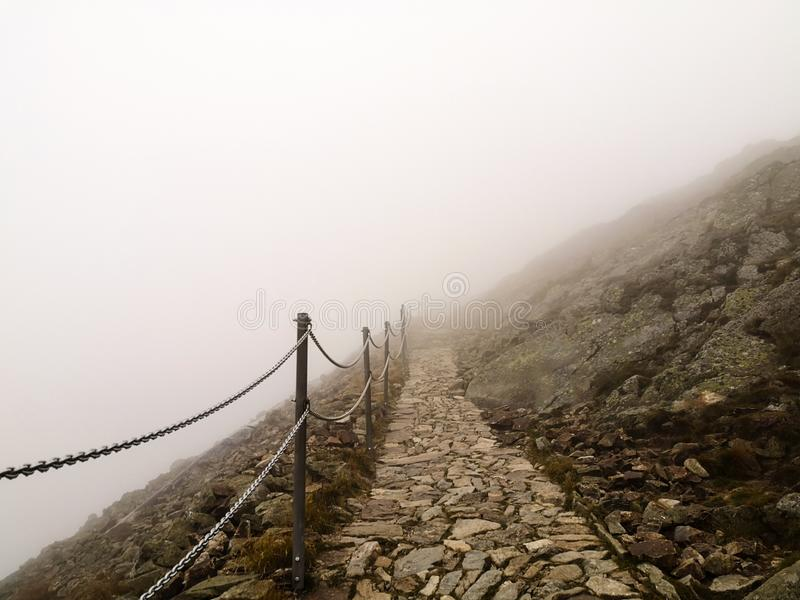 Rocky path with chain fence surrounded by thick mist on high mountains royalty free stock images