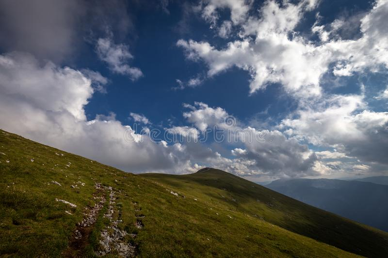 Rocky path in the fresh, green, grassy Rax plateau. With and dramatic, cloudy, blue sky to the Kaiserstein, peak of Schneeberg, Raxalpe, Alps, Lower Austria royalty free stock image