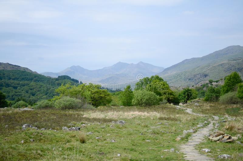 A rocky path winds across grassland towards trees and mountains in Snowdonia royalty free stock image