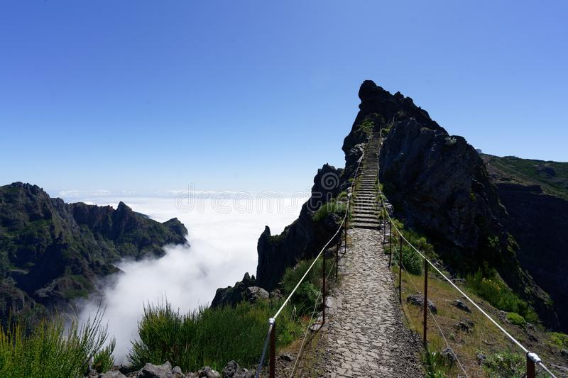 Rocky pathway towards the mountain top near the cliff with a clear blue sky in the background royalty free stock photo