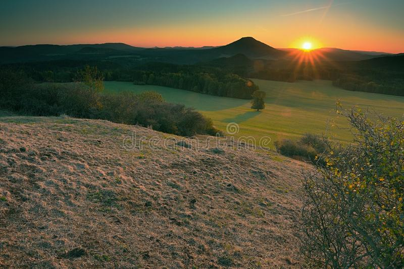 Rocky peak with daybreak. Full moon night ends and sun appeared. The rocky peak with daybreak. Full moon night ends and sun appeared in mist above hilly horizon stock photography