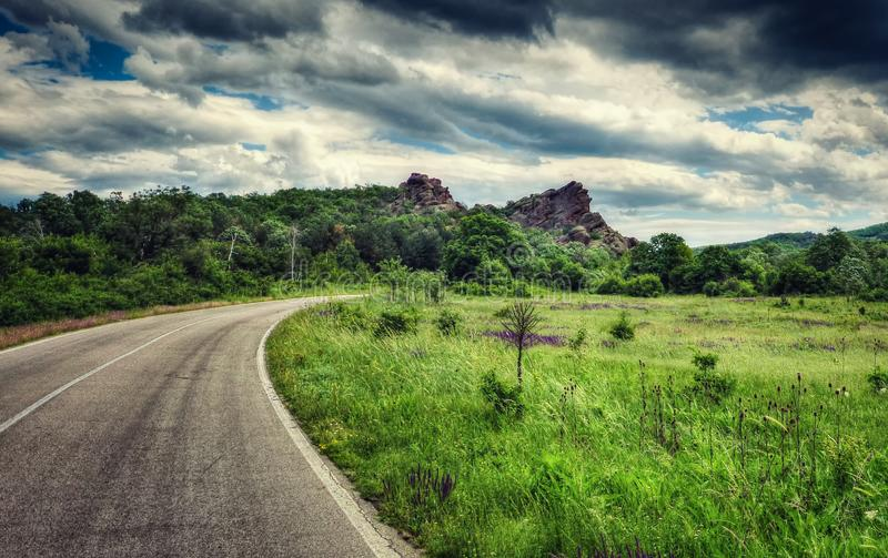 Rocky peak, forest, green meadow, turning road, dramatic sky stock photography