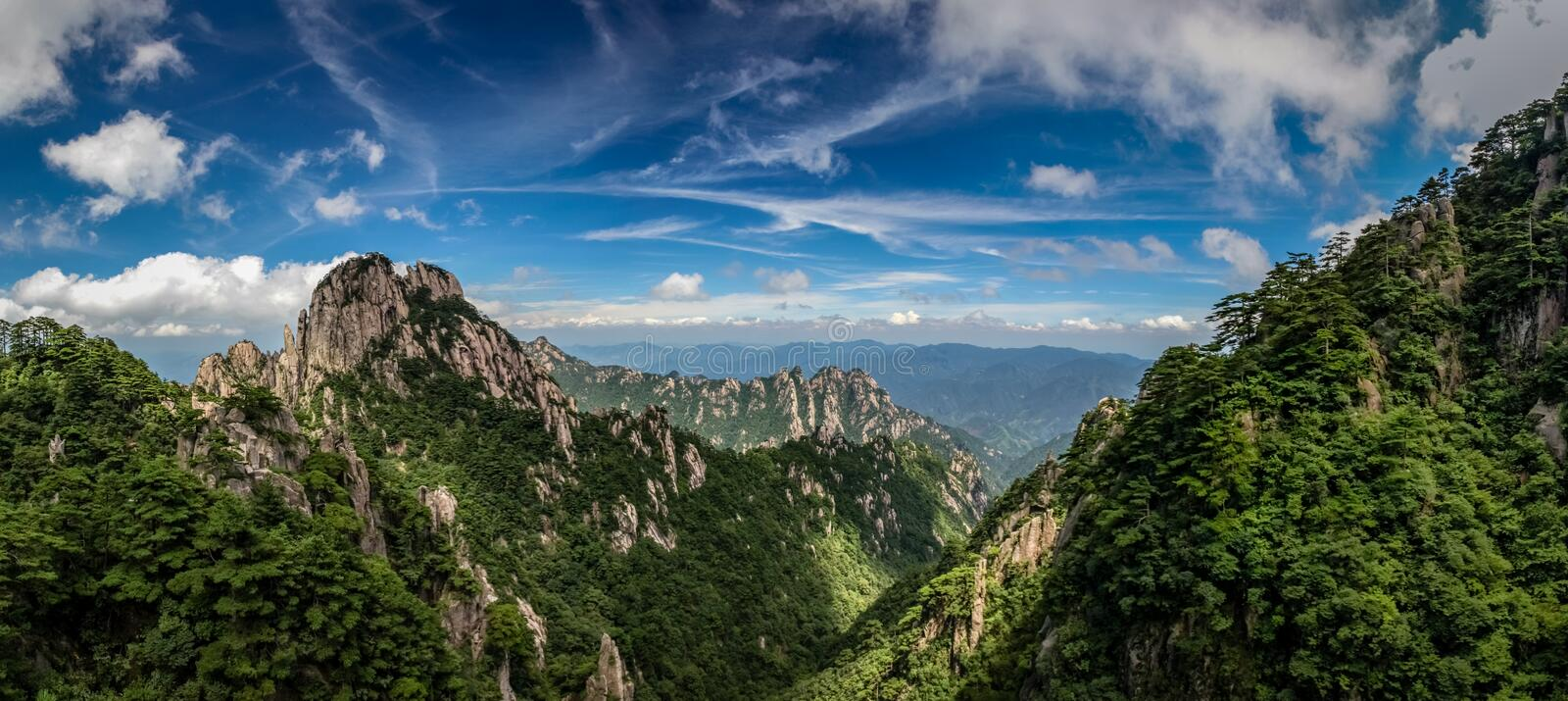 Rocky peaks and old pine trees cover the mountains under a bright blue sky with whispy clouds in Huangshan China stock photos